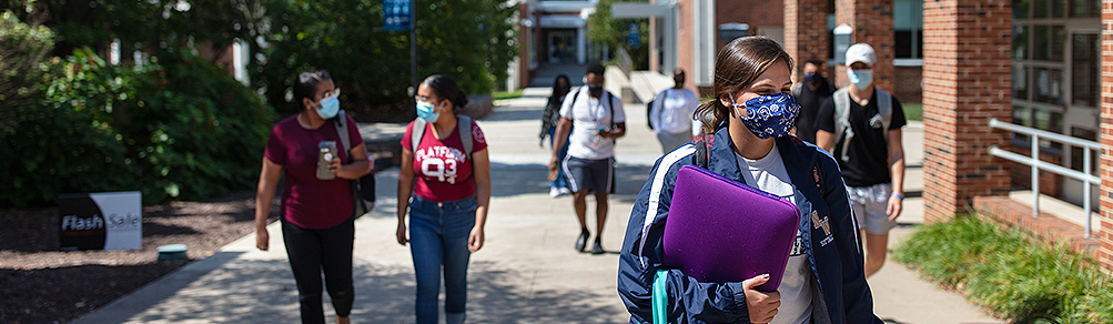 Group of students in masks walking along campus mall.