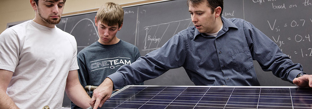 Students and instructor working on a solar panel.