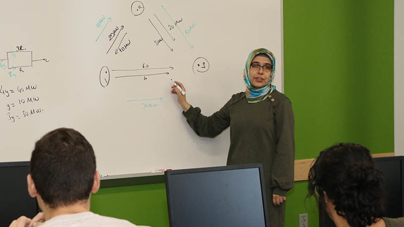 Penn State Hazleton Assistant Teaching Professor Mesude Bayrakci-Boz standing in front of a white board teaching with students in desks looking on.