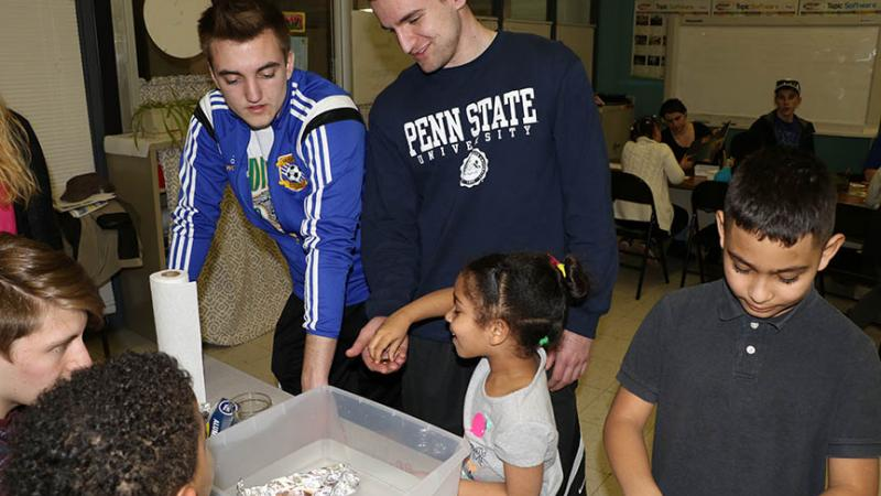 "Penn State Hazleton students work with the children on activities based on ""Daniel Finds a Poem."""