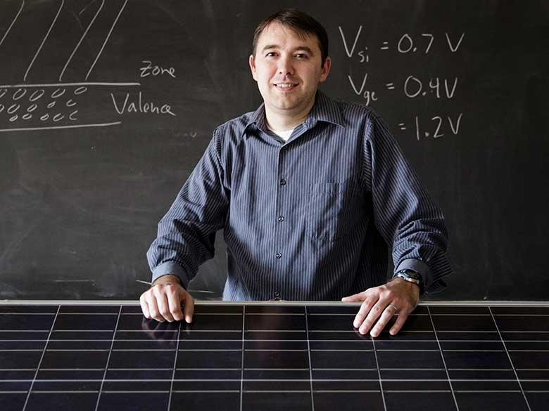 An engineering professor stands with a solar cell array.
