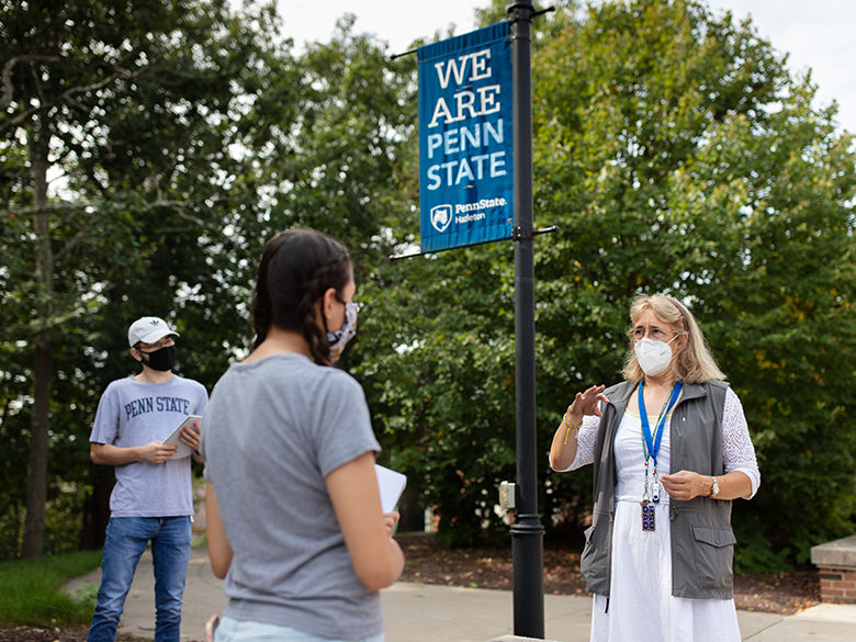 Students and an instructor in masks under a Penn State banner along the campus mall.