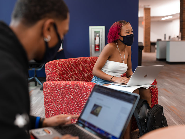 Students in masks studying in the library.