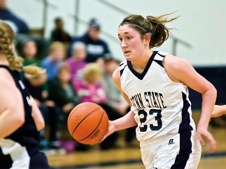 Female basketball player dribbling a basketball.