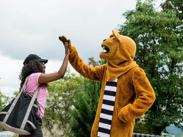 Hazleton lion high fiving student