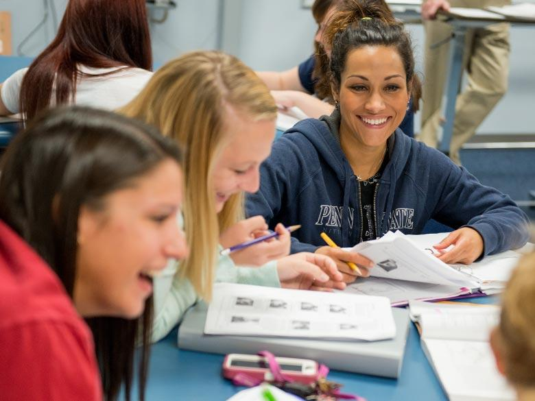 Students smiling at a desk