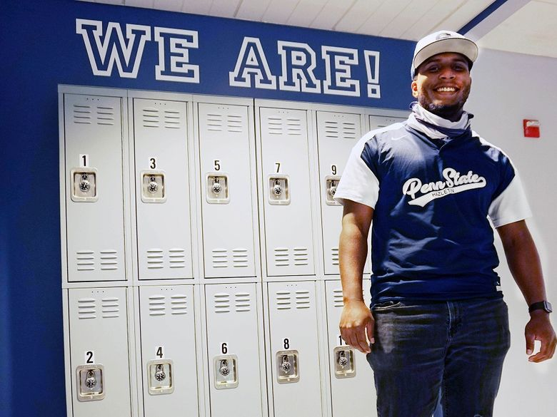 "Student standing in front of lockers with ""We Are"" on wall above."