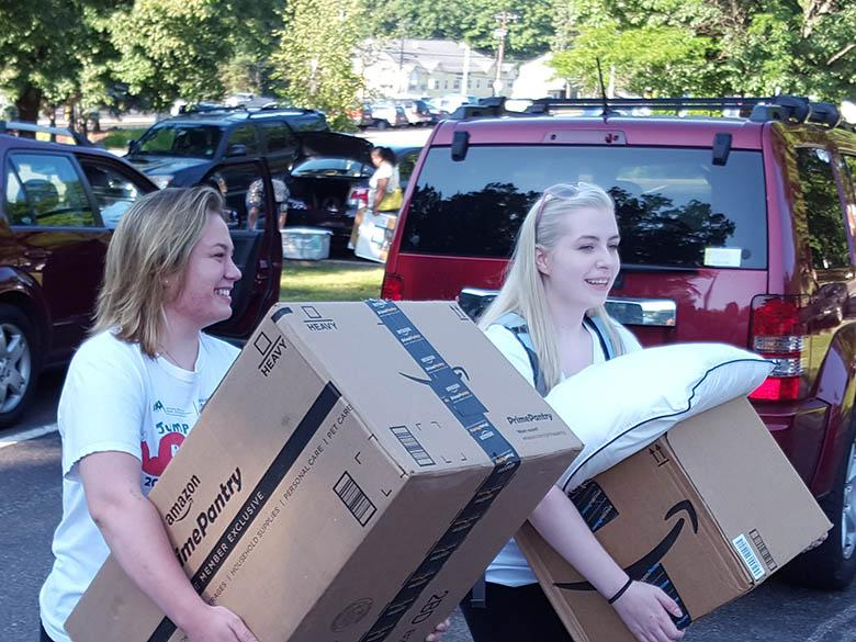 Students carrying boxes during move-in day.