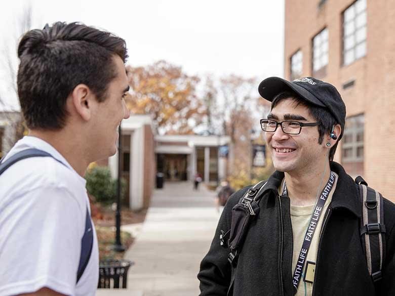 Two students speaking outdoors.
