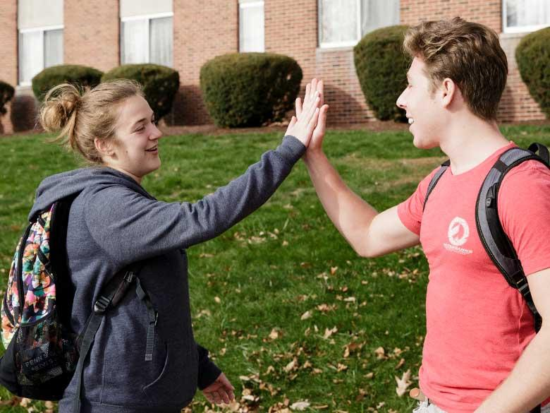 Two students high fiving.