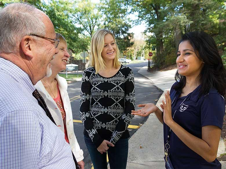 Penn State Hazleton student conducting a campus tour with a family.