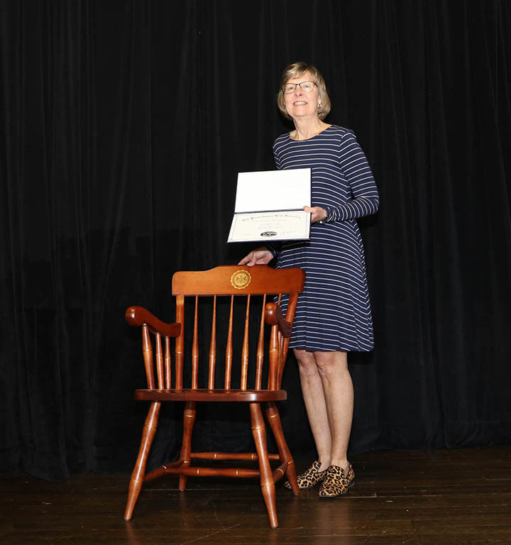 Woman holding certificate and standing in front of chair in front of a black curtain.