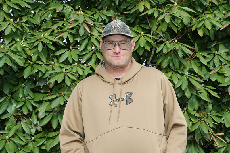 Man in hat and hooded sweatshirt standing in front of green trees.