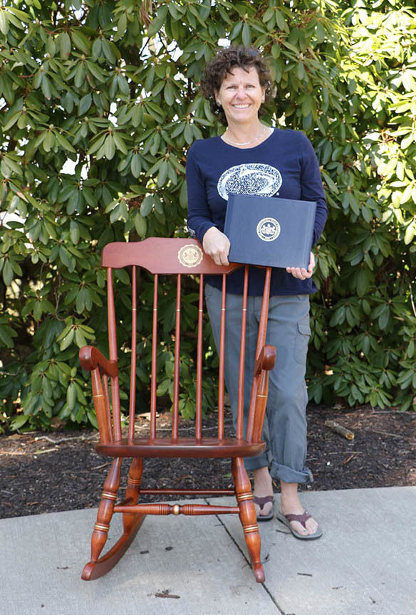 Woman standing in front of rocking chair holding a certificate.