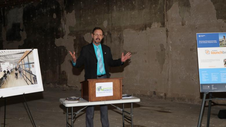 Man with hands out standing behind a podium