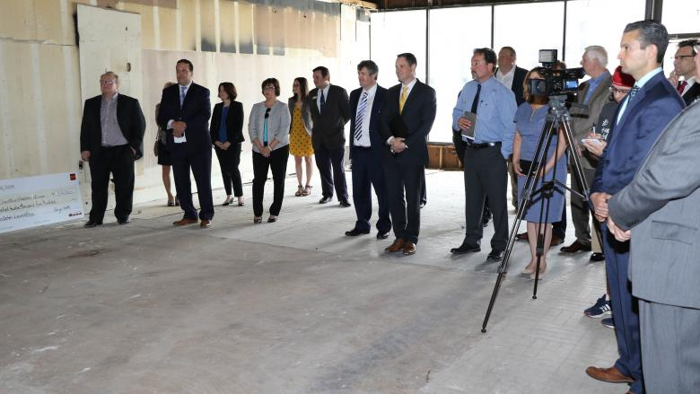 Group of people standing in a building undergoing renovation and watching a check presentation.