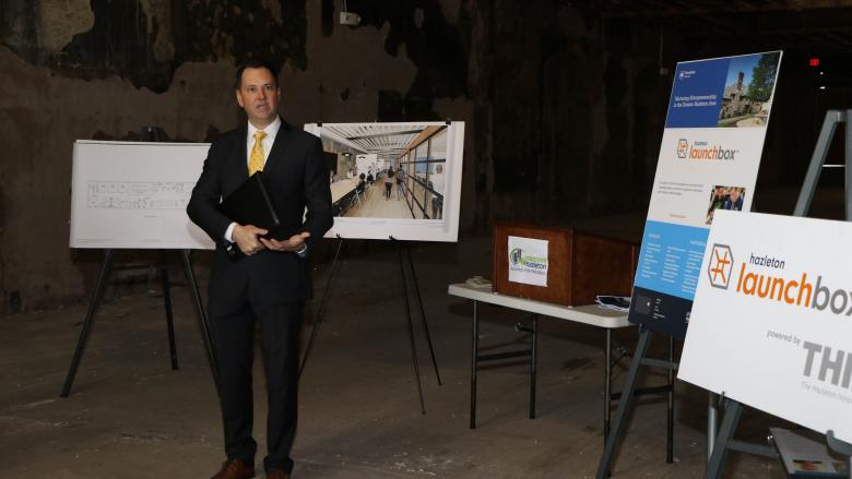 Man standing in a building undergoing renovation and talking to a group of people.