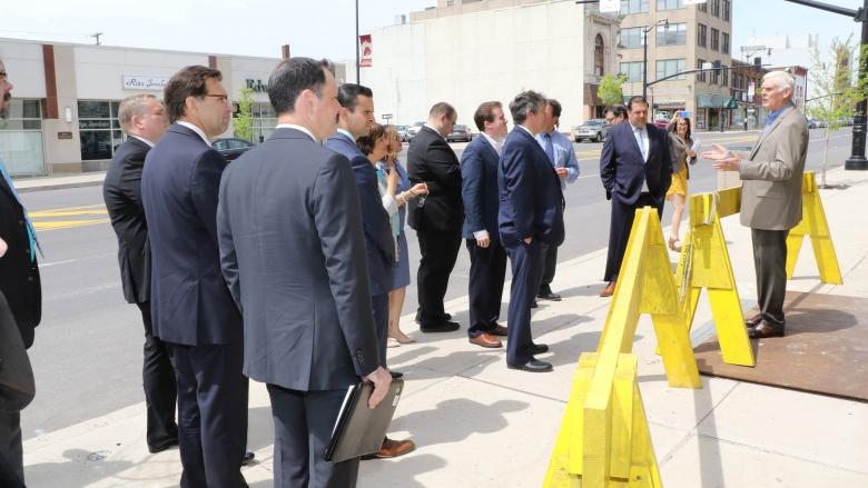 Man standing behind yellow construction barrier talking to a group of business people.