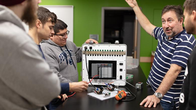 Ken Dudeck helps students use a new programmable logic controller (PLC).