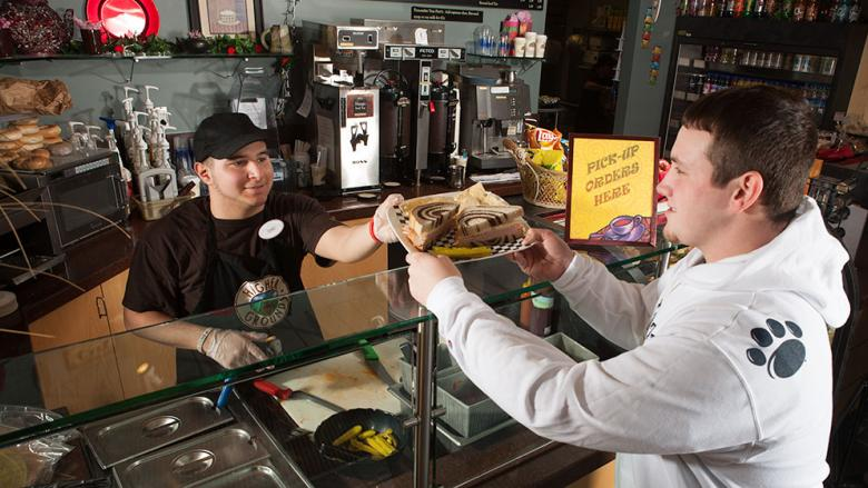 A student takes a sandwich from a student server at Higher Grounds.