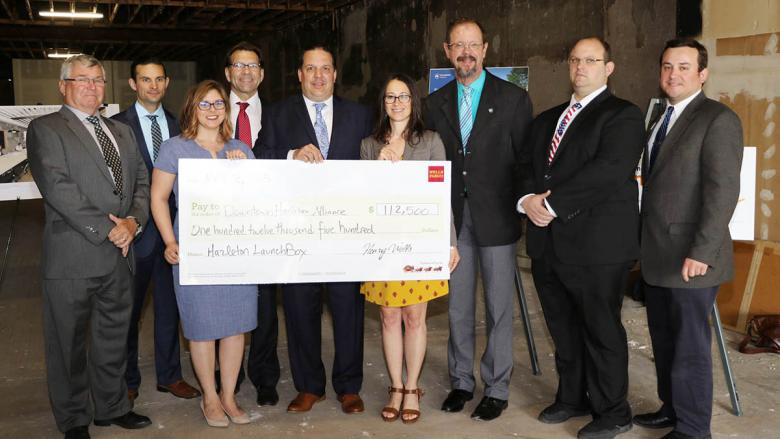 Group of business and community leaders standing and holding a large mock check.