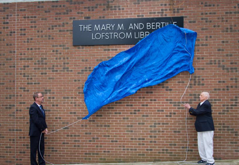 Penn State Hazleton Chancellor Gary Lawler and donor Bertil Lofstrom drop the banner revealing the new name of the campus library.